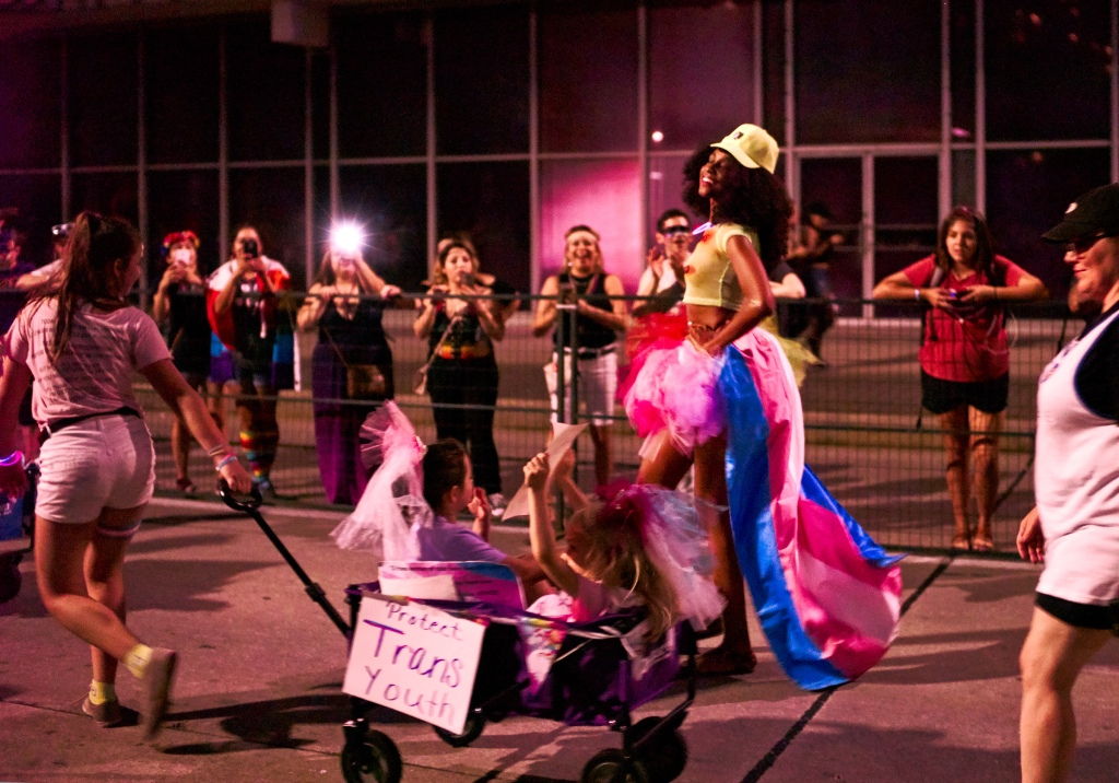 A picture of four people participating in a trans pride youth march. One is pulling a cart with two younger children inside. An older child is walking behind them in a tutu wearing a trans pride flag as a cape. There is a sign on the cart reading 'Protect trans youths'. A few people are watching the procession from behind a barrier.