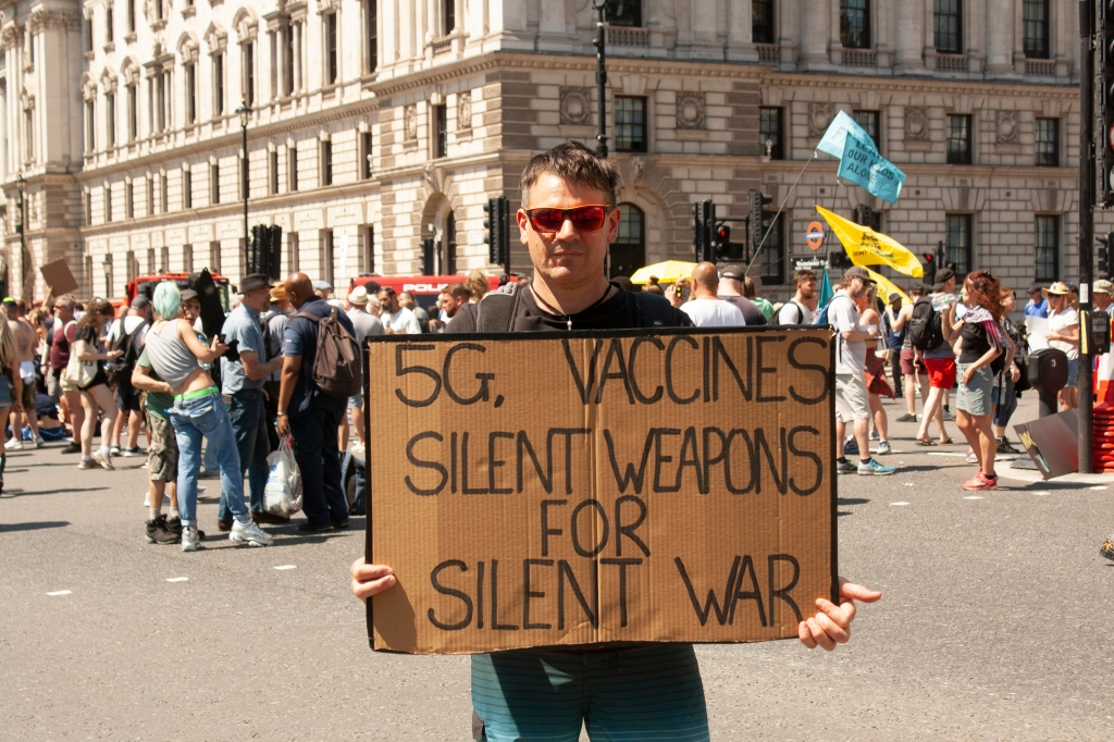A white man wearing sunglasses stands in a crowd holding a cardboard sign with the words: 5G, Vaccines, Silent Weapons for Silent War