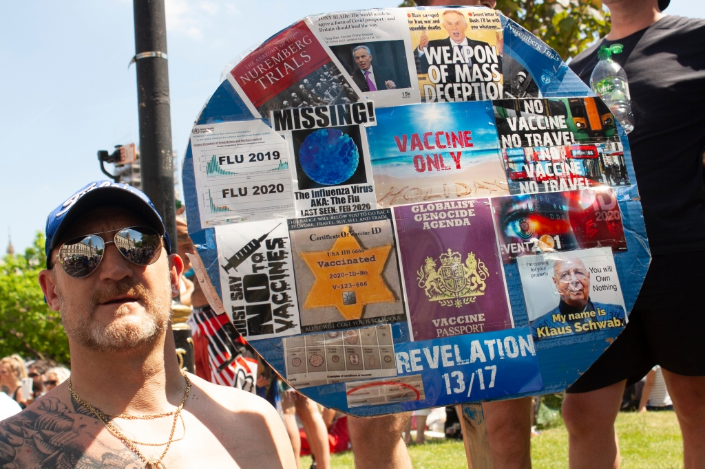 A shirtless white man wearing a baseball cap and aviator sunglasses holds up a round sign. On the sign are numerous printed pages which have been attached with sellotape. They are:  A graph of the number of flu cases in 2019 compared to 2020 'SAY NO TO VACCINES' in black ink A start of David, as worn by Jewish people during WW2, with overlaying text which reads: Certification of Vaccine ID and some random numbers. There is also an RFID chip embedded in the star. Brain scans Revalation 13/17 A fake British passport which reads: GLOBALIST GENOCIDE AGENDA VACCINE PASSPORT An influenza virus with the caption MISSING! The Influenza Virus AKA: The flu. Last Seen Feb 2020 A beach with the words: VACCINE ONLY HOLIDAY The cover of a book titled The Anatomy of the Nuremberg Trials Two pictures of Tony Blair - one from a news clipping with the headling: TONY BLAIR: The world needs to agree a form of Covid passport - and Britain should lead the way. And another with the words WEAPON OF MASS DESTRUCTION A picture of a London bus with the words NO VACCINE NO TRAVEL overlayed A picture of an eye with the words EVENT201 overlaid A picture of Klaus Schwab with the words I'm coming for your property You will Own Nothing overlayed