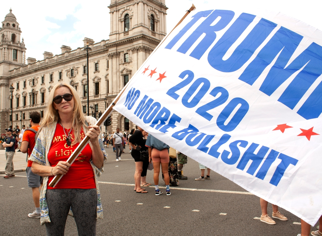 A white woman wearing aviator sunglasses (are you noticing a pattern here?) holds a white flag which reads: TRUMP 2020 NO MORE BULLSHIT