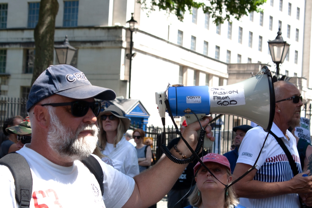 A white man in a crowd wearing sunglasses and a baseball cap holds up a bullhorn with the words 'On A Mission From God' stuck to it.