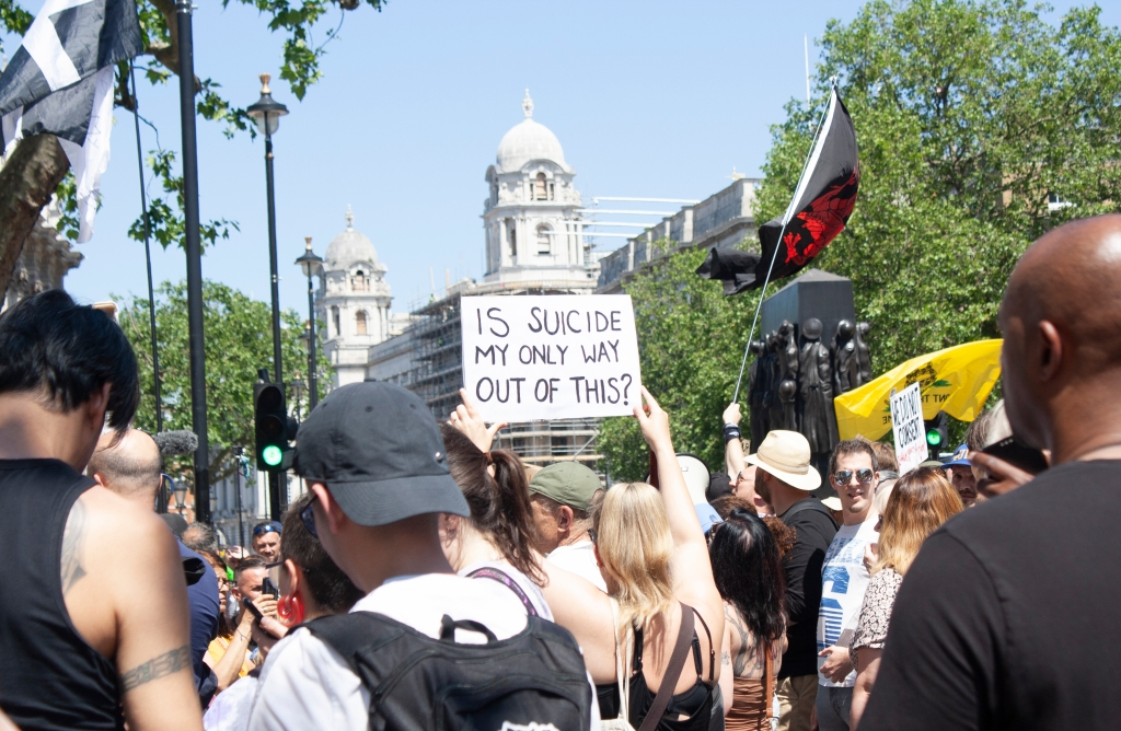 A white woman is standing with her back turned to camera in the middle of a crowd. She is holding a white sign which reads: IS SUICIDE MY ONLY WAY OUT OF THIS?
