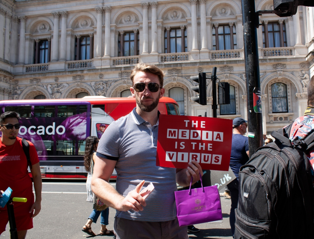 A white man with aviator sunglasses and a blue and white striped shirt stands on a London street holding a red  and white sign which reads: THE MEDIA IS the VIRUS. The font is deliberately evocative of the BBC branding.